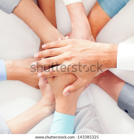 A group of people showing their unity by putting their hands one on top of the other. - stock photo