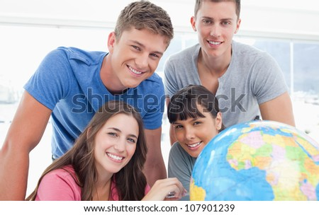 A group of people smiling as they all look into the camera with a globe next to them - stock photo