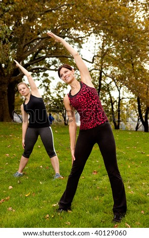 A group of people stretching in a park - focus on front woman - stock photo