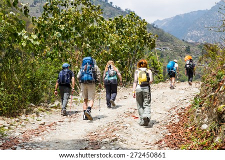 A group of people trekking on dirt road in Nepal - stock photo