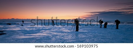 A group of photographers set up on the frozen surface of Lake Michigan at dawn to photograph the Cana Island Lighthouse in Door County, Wisconsin. - stock photo