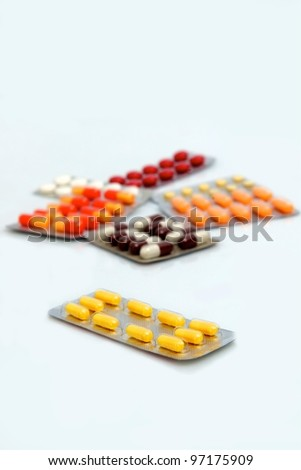 a group of pills, with yellow pills in focus - stock photo