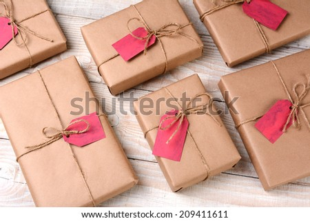 A group of plain brown paper wrapped Christmas presents on a white wood table. The gifts are tied with twine and have blank red gift tags. High angle shot. - stock photo