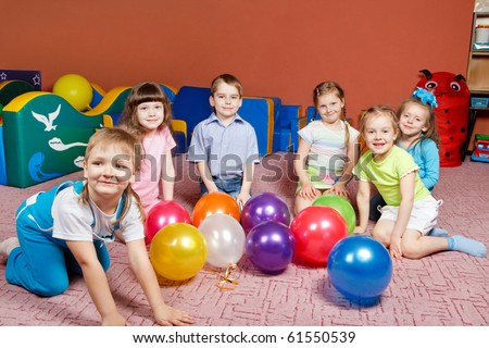 A group of preschool kids in kindergarten with balloons on the floor - stock photo