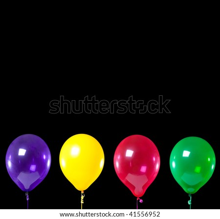 A group of primary colored party balloons on a black background with copy space