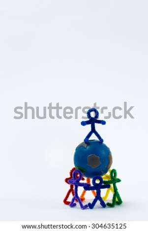 A group of rainbow pipe-cleaner people holding the world. They are working together to make a more peaceful world or to fix the world. This could be used for many ideas and concepts around the world. - stock photo