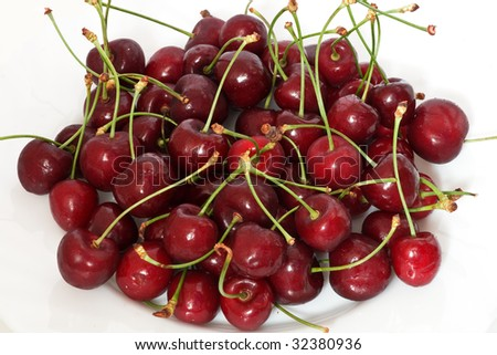 a group of ripe cherries on o white plate