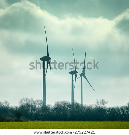 A group of rotating wind energy wheels against the cloudy sky in Germany.  - stock photo