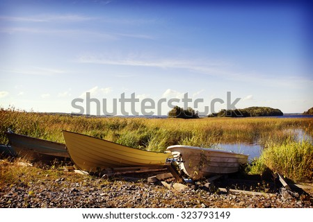 A group of rowing boats on the beach by the lake in the autumn. The focus point is on the boats in the front part. Image also has a vintage effect applied. - stock photo