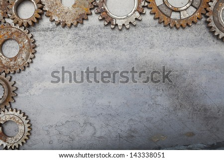 A group of rusty gears framing a grungy metal background. - stock photo