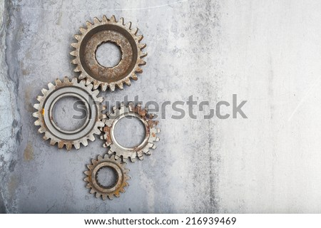 A group of rusty gears linked together on a steel background. There is plenty of room left for your copy. - stock photo
