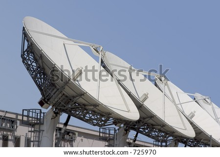 A group of satellite dishes point skyward. - stock photo