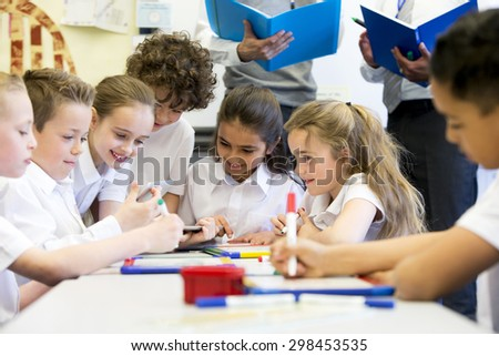 A group of school children can be seen working on digital tablets and whiteboards, they are all working happily. Two unrecognizable teachers can be seen in the background. - stock photo