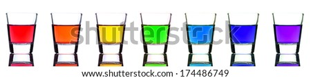 A group of shot glasses with a rainbow of colored drinks.