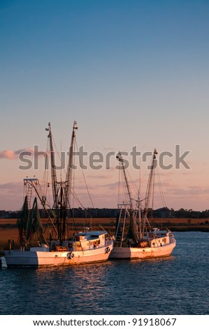 A Group of Shrimping Boats Wait at the Dock in the Evening - stock photo