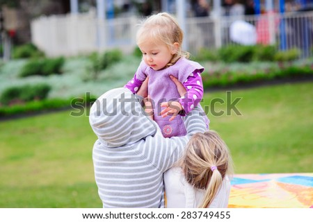 A group of siblings with big brother and sister holding their little toddler sister - stock photo