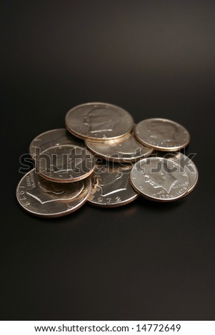 A group of silver dollars and half dollars isolated on a black background - stock photo