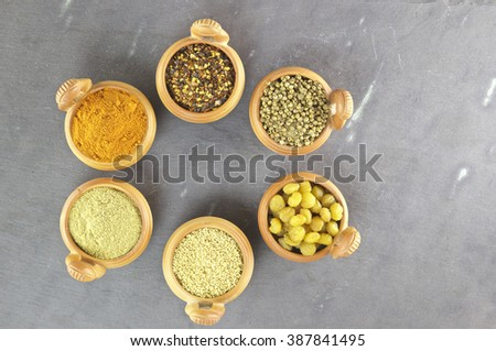A group of six brown bowls with very colorful spices on a slate plate. - stock photo