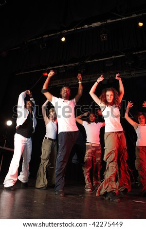 A group of six female and male freestyle hip-hop dancers during dance training session on stage. Lit with spotlights