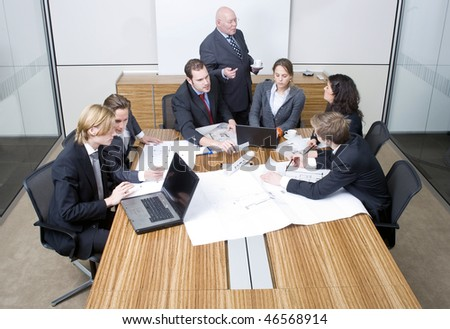 A group of six junior associates during a design team meeting with a senior manager