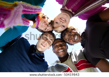 A group of smiling faces of multi-racial college students/friends outside with the blue sky in the background - stock photo