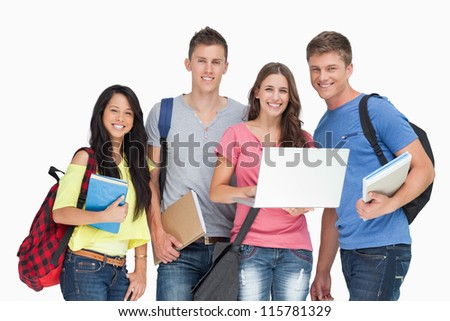 A group of smiling students looking at the camera while one holds a laptop - stock photo