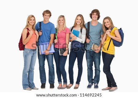 A group of smiling students stand beside each other and wear backpacks and hold notepads while looking at the camera - stock photo