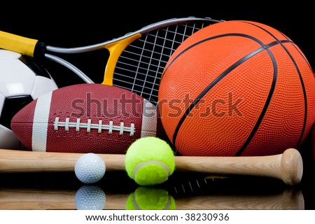 A group of sports equipment on black background including tennis, basketball, baseball, american fotball and soccer and boxing equipment on a black background with copy space - stock photo