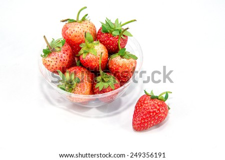 A group of strawberry in a bowl and one