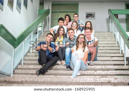 A group of students posing on school stairs sitting - stock photo