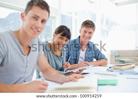 A group of students sit together at the table and look into the camera - stock photo