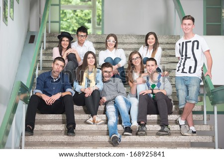 A group of students sitting on school stairs smiling - stock photo