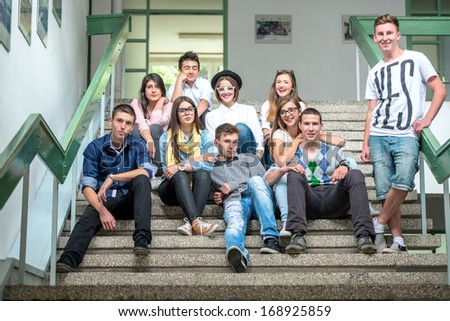 A group of students sitting on school stepss posing - stock photo