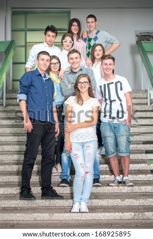 A group of students standing on school stairs posing - stock photo