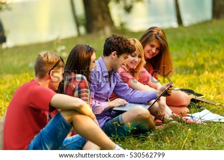 a group of students with laptop relaxing in the Park on a Sunny