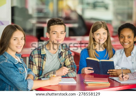 A group of teenagers sitting at the table in cafe and doing homework.