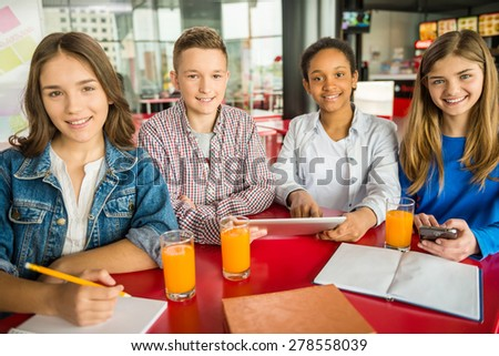 A group of teenagers sitting at the table in cafe, studying and drinking orange juice. - stock photo