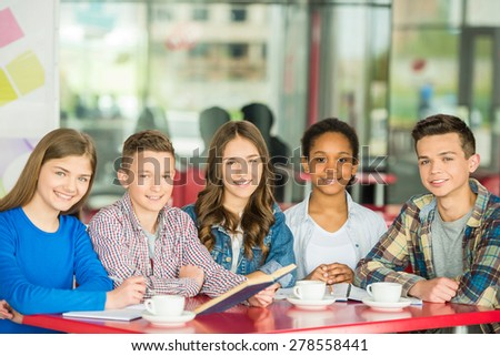 A group of teenagers sitting at the table in cafe, studying and drinking tea. - stock photo
