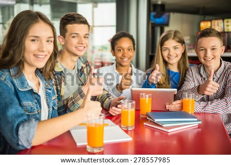 A group of teenagers sitting at the table in cafe, using digital tablet and drinking orange juice. - stock photo