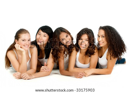 A group of teenagers with diverse ethnicities lying down against white background - stock photo