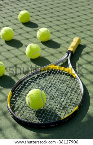 A group of tennis balls and a tennis racket on a freshly painted cement tennis court - stock photo