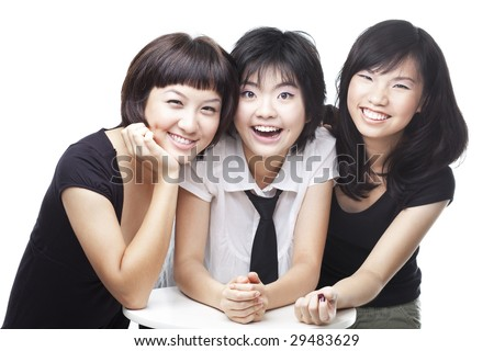 A group of three asian Chinese teenagers friends in college sharing a laughing, happy moment - stock photo