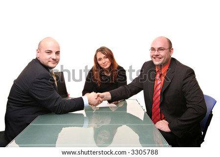 A group of three at a table. Two men shaking hands. Isolated on a white background - stock photo