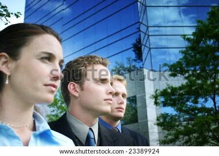A group of three business people standing together outside against a blue business building in their business suits and business clothes - stock photo