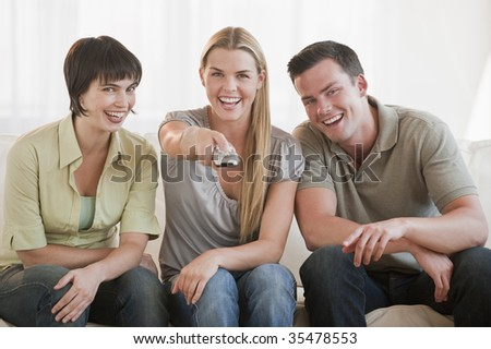A group of three friends are sitting on a couch together and watching TV.  They are smiling at the camera.  Horizontally framed shot. - stock photo
