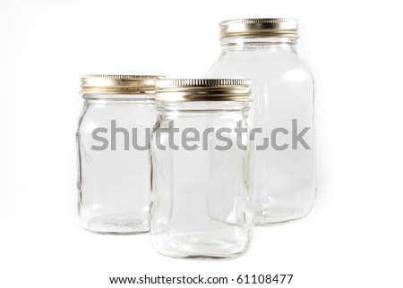 A group of three glass mason jars for canning on a white isolated background.