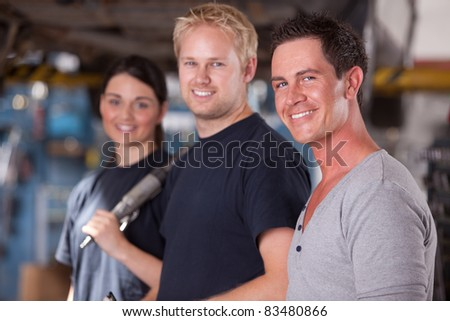 A group of three mechanics in a auto repair shop, looking at the camera - stock photo