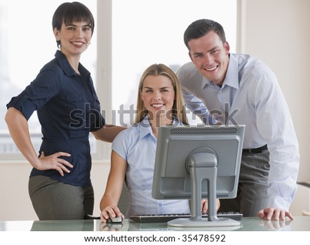 A group of three people are working together on a computer.  They are smiling at the camera.  Square framed shot. - stock photo
