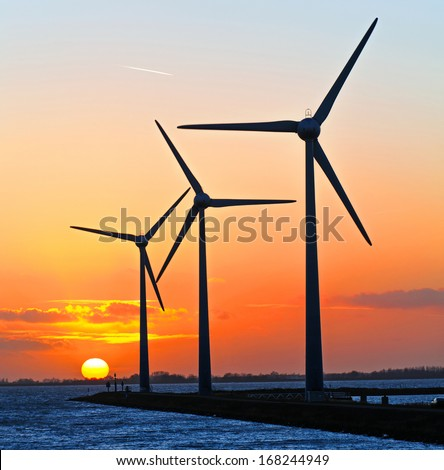A group of three wind turbines at sunset - stock photo