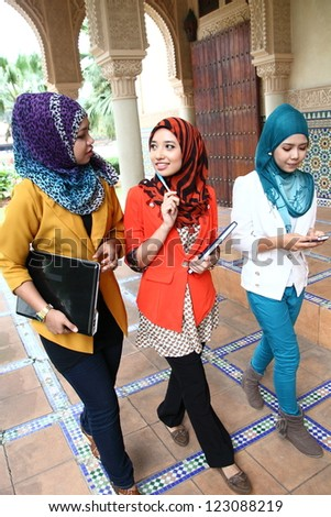 A group of three young muslim girls chatting and walking together - stock photo